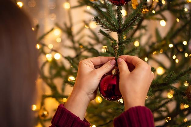 Vista traseira de uma menina morena com suéter cor de vinho, pendurando uma bola vermelha na árvore de natal Foto Premium