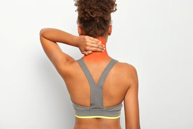 Vista traseira de uma mulher de pele escura e cacheada tocando o pescoço, sente dor, precisa de massagem, sofre de lesão muscular, usa blusa cinza, isolada na parede branca Foto gratuita