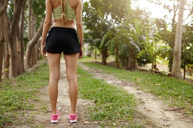 Vista traseira do atleta jovem loira em tênis-de-rosa em pé no parque ou floresta em caminho com árvores verdes ao redor. Foto gratuita