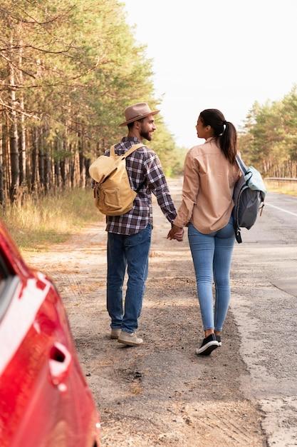 Vista traseira do casal caminhando com as mochilas nas costas Foto gratuita