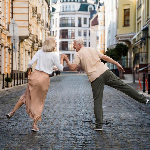 Vista traseira do casal feliz mais velho na cidade Foto Premium