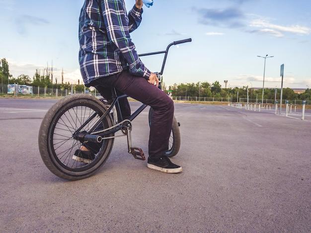 Vista traseira do corpo do adolescente sentado relaxando na bicicleta bmx Foto Premium