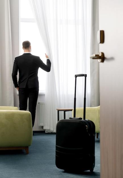 Vista traseira do empresário vestindo um terno escuro em pé no quarto do hotel, olhando pela janela Foto Premium