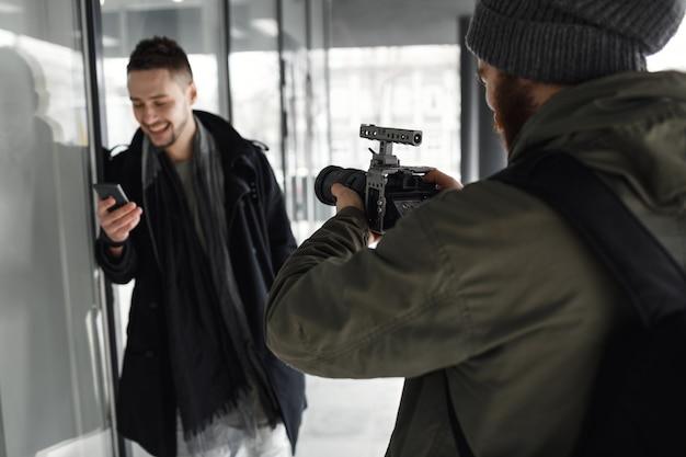 Vista traseira do fotógrafo tiro modelo masculino bonito lá fora. Foto gratuita
