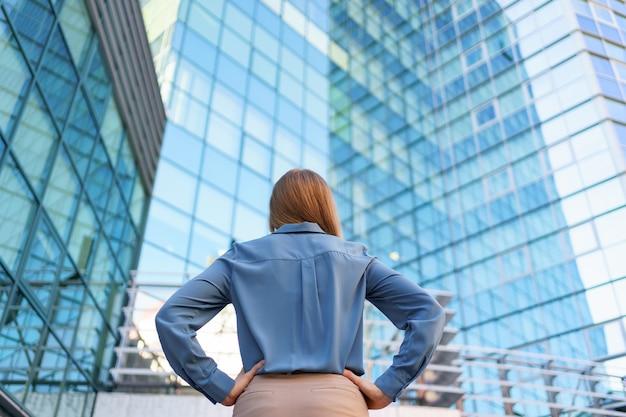 Vista traseira do gerente bem-sucedido, olhando para o edifício comercial da cidade moderna. Foto gratuita