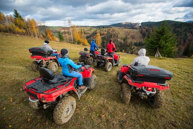 Vista traseira do grupo de cinco pessoas andando de bicicleta quad na colina e apreciando a bela paisagem de outono Foto Premium