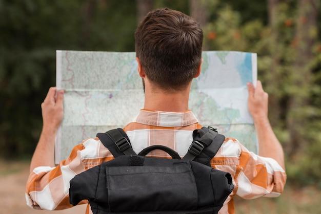 Vista traseira do homem com mochila olhando o mapa enquanto acampa Foto gratuita