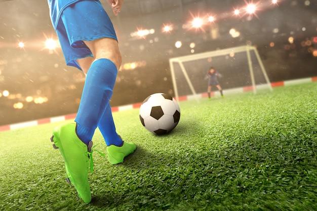 Vista traseira do homem jogador de futebol chutando a bola no campo de futebol Foto Premium