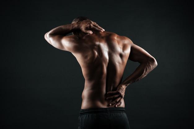 Vista traseira do homem jovem esportes africanos, sentindo dor nas costas Foto gratuita