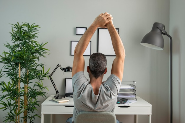 Vista traseira do homem na mesa se alongando enquanto trabalhava em casa Foto gratuita