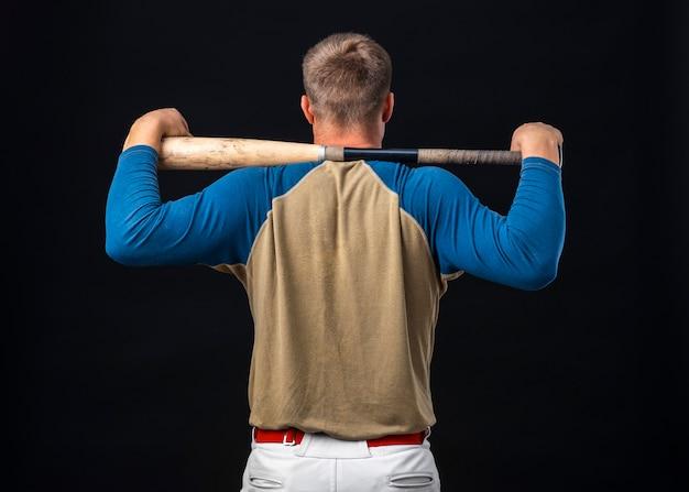 Vista traseira do jogador de beisebol segurando o bastão Foto gratuita