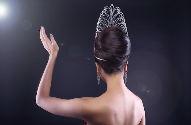 Vista traseira do lado traseiro retrato do concurso de beleza miss pageant com mão de onda de coroa de diamante Foto Premium