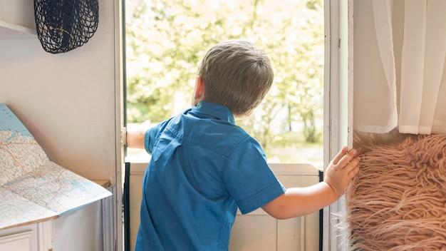 Vista traseira do menino abrindo a porta de um trailer Foto gratuita