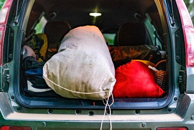 Vista traseira do porta-malas aberto cheio de malas no acampamento da natureza. Foto Premium