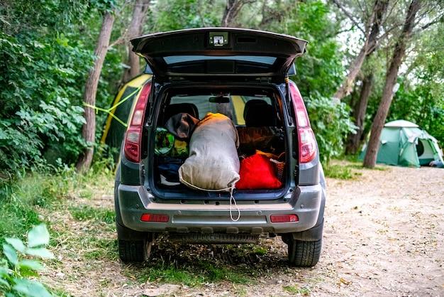 Vista traseira do porta-malas aberto cheio de sacos de bagagem em natureza campp. Foto Premium