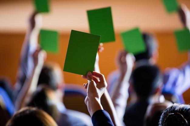 Vista traseira dos executivos mostra sua aprovação levantando as mãos Foto gratuita