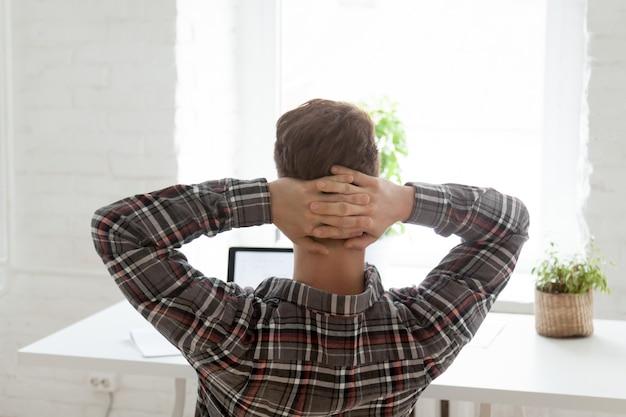 Vista traseira, em, relaxado, homem, descansar, de, trabalho, ligado, laptop Foto gratuita