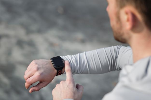 Vista traseira homem ajustando seu relógio de esporte Foto gratuita