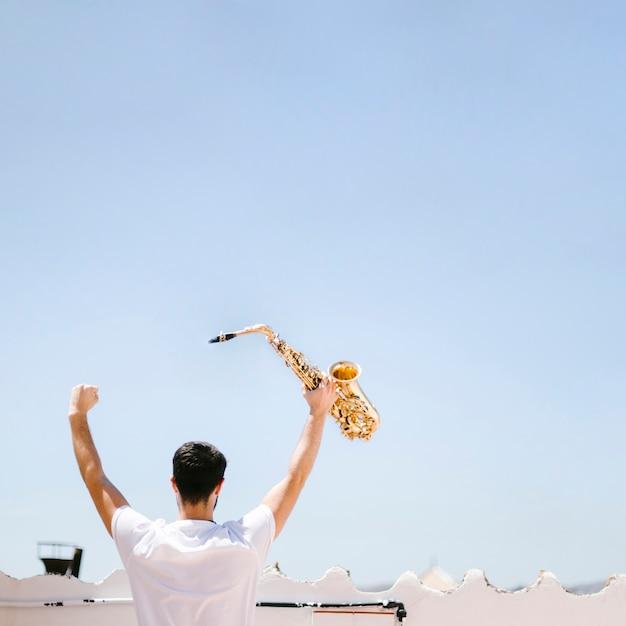 Vista traseira homem segurando saxofone Foto gratuita