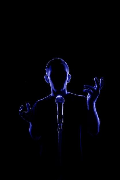 Vista traseira iluminada de um homem sem rosto conversando ou cantando ao microfone Foto Premium