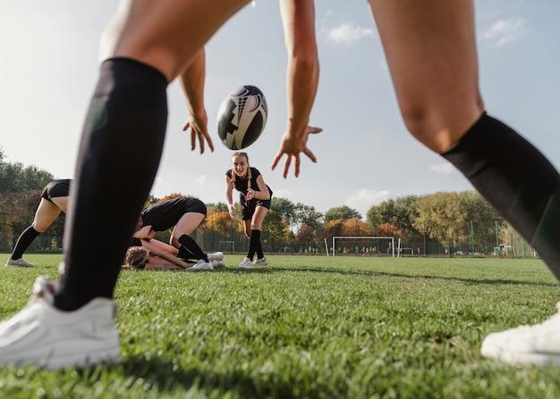 Vista traseira mãos de mulheres tentando pegar uma bola de rugby Foto gratuita