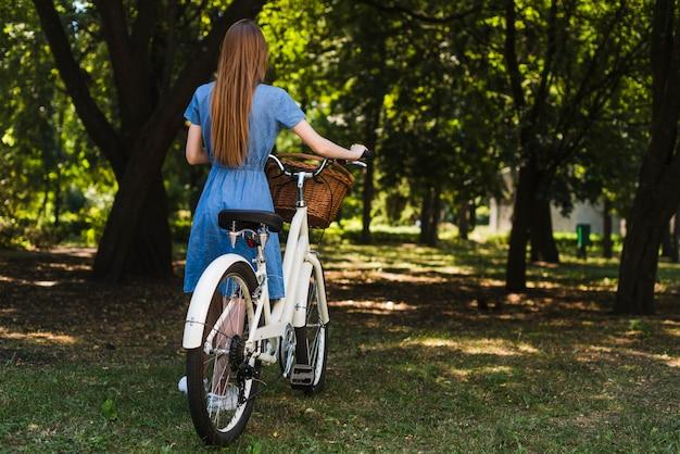 Vista traseira, mulher caminhando, perto, bicicleta Foto gratuita