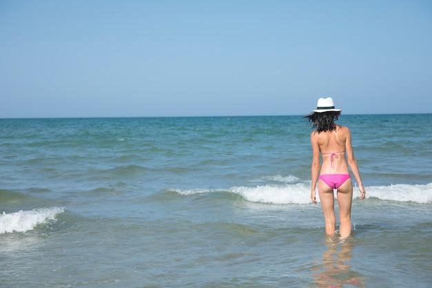 Vista traseira, mulher, ficar, em, água, em, praia Foto gratuita
