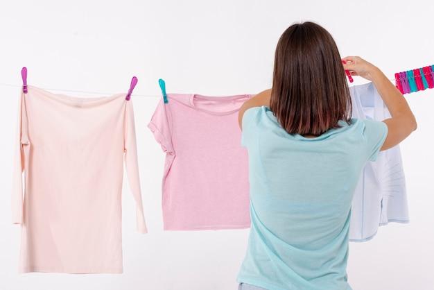 Vista traseira, mulher, organizando roupas, ligado, varal Foto gratuita