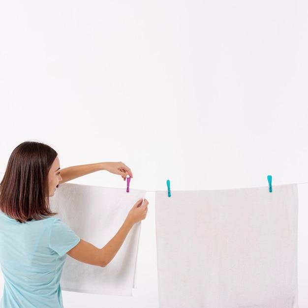 Vista traseira, mulher, organizando, toalhas, ligado, varal Foto gratuita