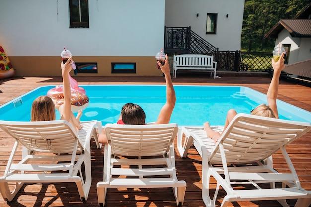 Vista traseira, pessoas, em, praia, loungers Foto gratuita