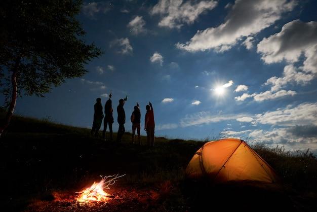 Vista traseira silhuetas de jovens levantados garrafas sob o céu azul com o sol brilhante Foto Premium
