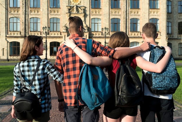 Vista traseira, tiro médio, de, abraçando, adolescentes, ir escola secundária Foto gratuita