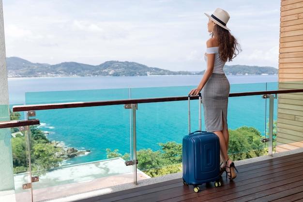 Vista traseira: uma bela turista com uma figura luxuosa de chapéu posa com sua bagagem na varanda, que oferece uma bela vista do mar e das montanhas. viagens e férias. Foto Premium