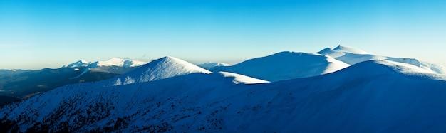 Vistas hipnotizantes de cadeias de montanhas cobertas de neve com o pôr do sol e o céu nublado ao fundo Foto Premium