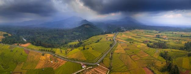 Vistas panorâmicas de campos de arroz a partir de belas fotos aéreas do pôr do sol nublado com o monte bengkulu utara, indonésia Foto Premium
