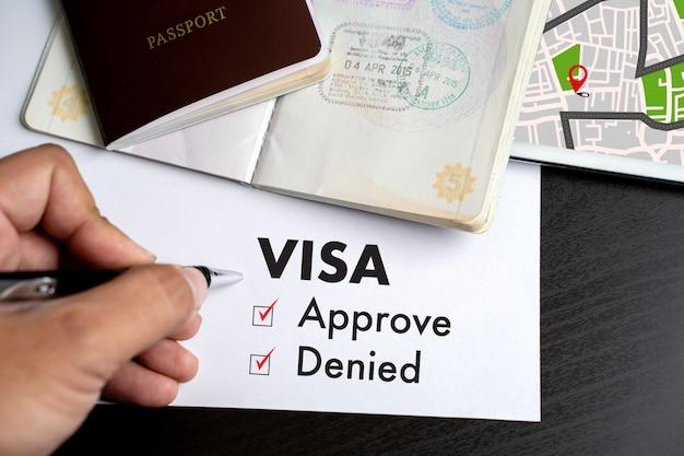 Visto e passaporte para aprovado carimbado em uma visão de topo do documento em visto de imigração aprovar Foto Premium