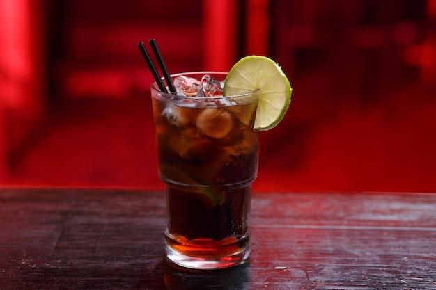 Visualização horizontal. close de um coquetel cuba libre em copo longo, gim, em pé no balcão do bar, isolado em um espaço vermelho. Foto Premium