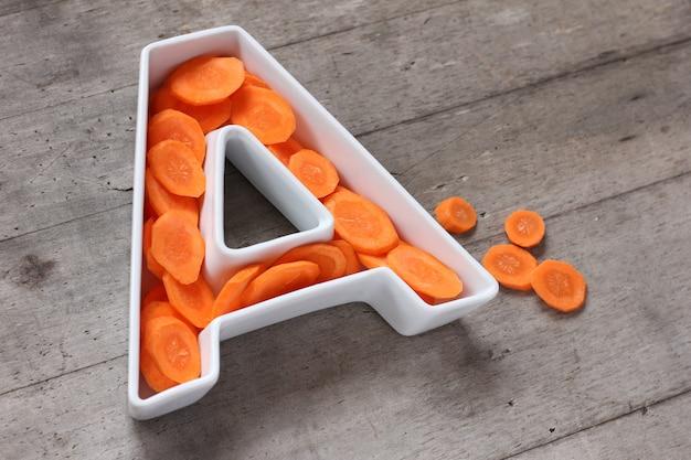 Vitamina a no conceito de comida. placa em forma de letra a com cenouras frescas em fatias. Foto Premium