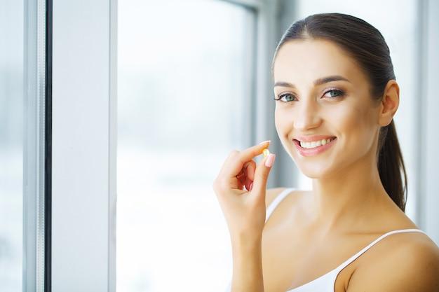 Vitaminas. alimentação saudável. menina feliz com a cápsula do óleo de peixes omega-3. conceito de dieta saudável. Foto Premium