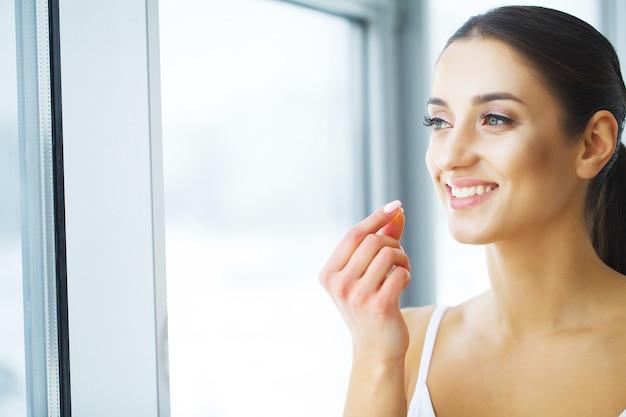 Vitaminas. alimentação saudável. menina feliz com cápsula de óleo de peixe omega-3. conceito de dieta saudável. Foto Premium