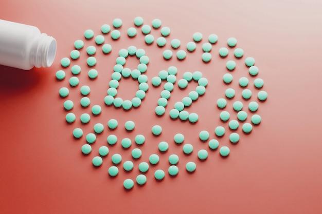 Vitaminas b 12 em forma de coração em um substrato vermelho, derramado de um frasco branco. Foto Premium