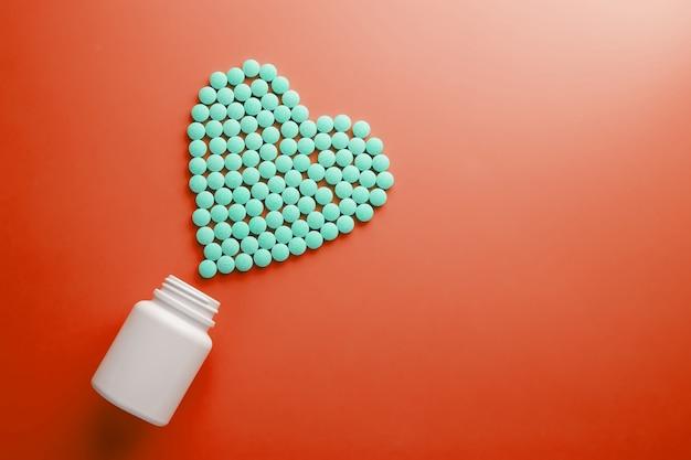 Vitaminas b 12 em um substrato vermelho em forma de coração, derramado de um frasco branco. Foto Premium