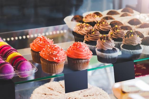 Vitrine com doces no café. cupcakes e macaroons coloridos no visor do bolo Foto Premium