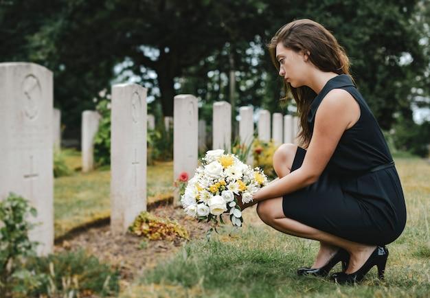 Viúva jovem colocar flores no túmulo Foto Premium