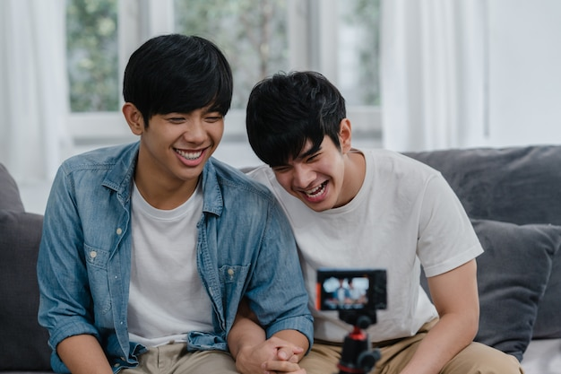 Vlog gay asiático novo dos pares do influenciador dos pares em casa. os homens lgbtq coreanos adolescentes felizes relaxam o divertimento usando o upload de vídeo do vlog de registro de câmera nas mídias sociais enquanto estão deitados no sofá na sala de estar em casa. Foto gratuita