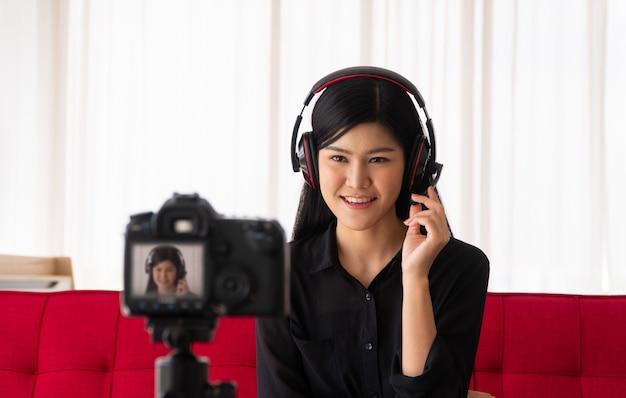 Vlog mulher asiática blogueira influenciadora sentada no sofá em casa gravando videoblog para ensinar e treinar seus alunos Foto Premium