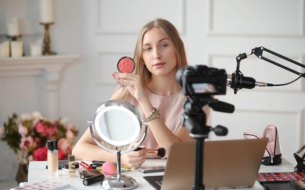 Vlogger de beleza. jovem gravando um tutorial de maquiagem Foto gratuita