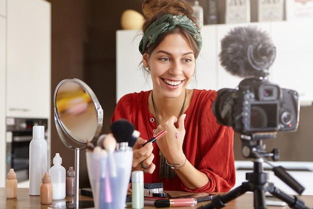 Vlogger feminina filmando vídeo de maquiagem Foto gratuita
