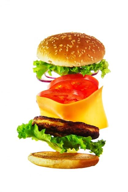 Voando ingredientes para um hambúrguer caseiro. Foto Premium