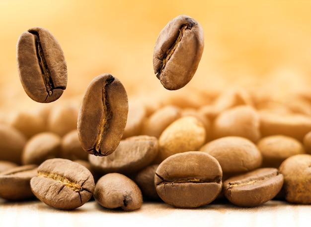 Voar grãos de café frescos no fundo desfocado amarelo com espaço de cópia. Foto Premium